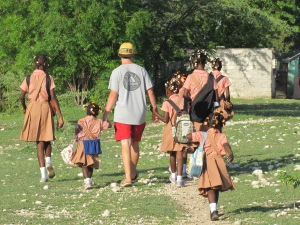 Jacob walking the children to school on their first day of school in their new home.