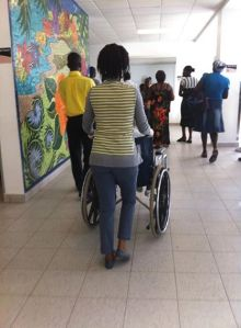 Marc Julimesse pushing Gislene through the hospital in a wheelchair