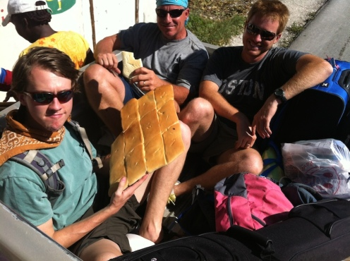 All the guys in the back of the truck munchin' on bread on the way to the beach.