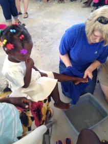 Debbie washing Miliene's feet at Women's Bible Study