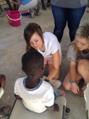 Jenny and Madison wash a child's feet who came with his mom to Women's Bible Study
