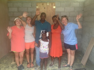 Some of the girls from the Natchez team with Nicoderm and his family after they built their house